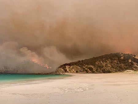 Photograph of Western River Cove, Kangaroo Island looking from beach across the water as fire engulfs headland. Smoky sky an eerie orange-pink. For sale in the virtual exhibition.